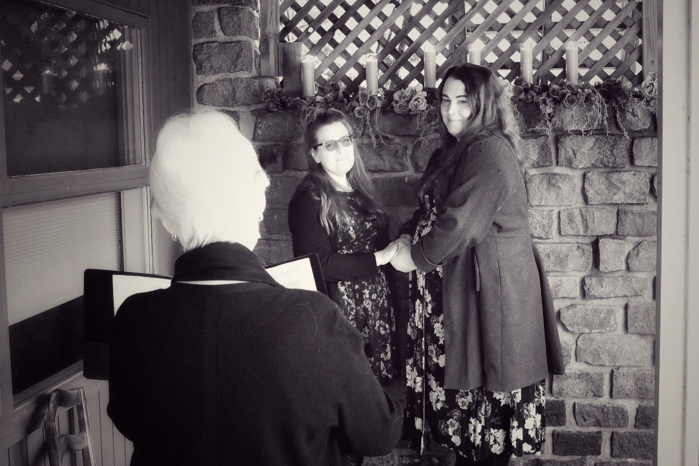 Holly and Jina holding hands and looking at the officiant.