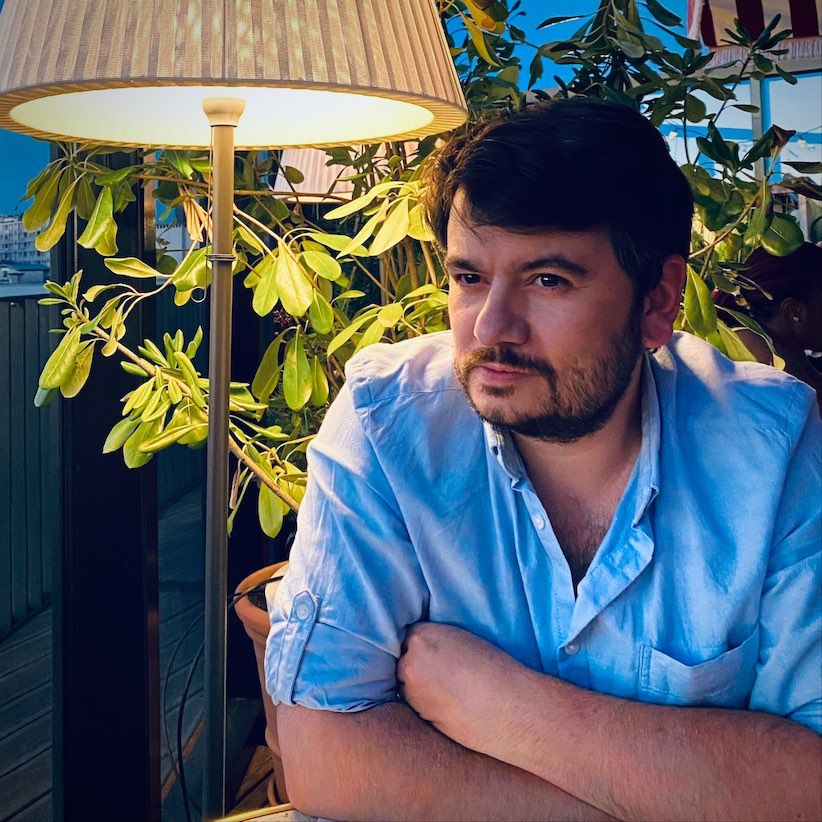 Medium shot, colour portrait of myself, Nicolas Magand, without glasses and with a blue shirt.