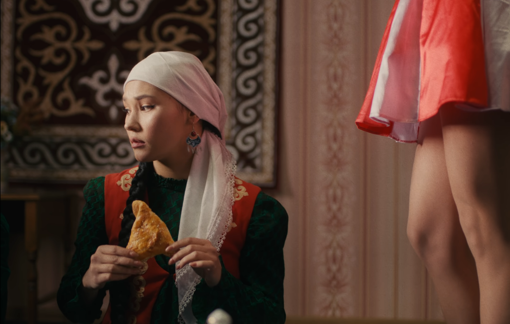 Image of a young woman dressed conservatively and wearing a headscarf, holding a samosa-like pastry, with the American in the stars-and-stripes dress standing mostly offscreen