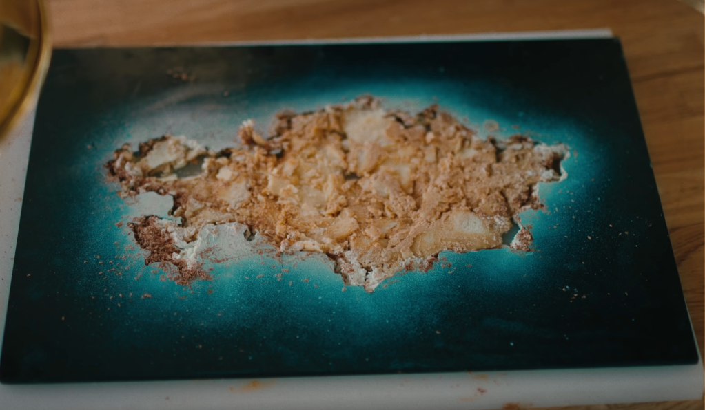 Image of a plate with crumbs lying in the middle of a blue template with the shape of Kazakhstan cut out of it