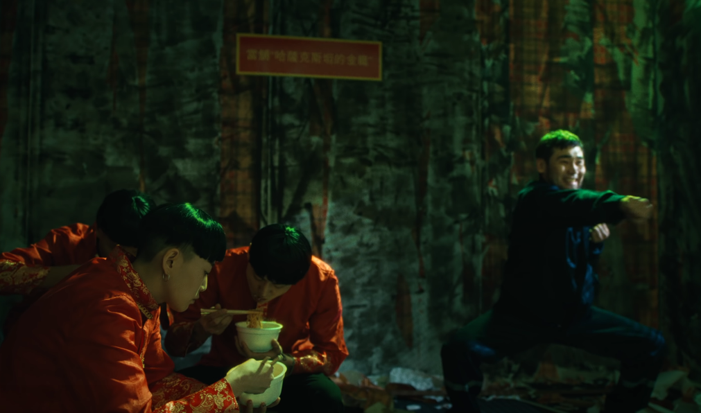 Image of Hiro in a blue outfit doing exercises and grimacing while the three people in bowl cuts eat noodles, with a sign in Chinese characters in the background