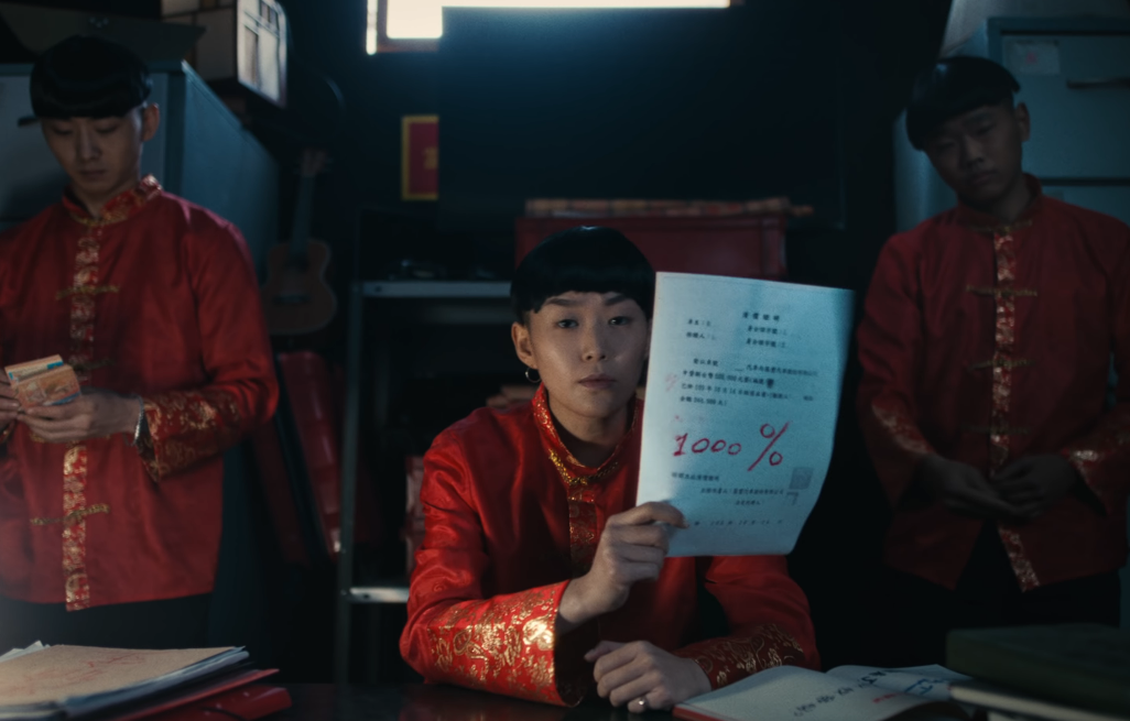 "Image of three people in bowl cuts and red-and-gold jackets, one of them counting money and one of them holding up a piece of paper on which ""1000%"" is written large in red ink"
