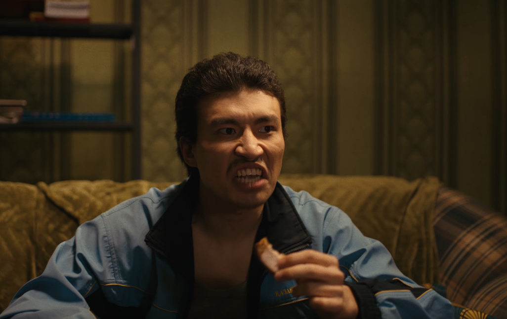 Image of Amazat dressed as the Kazakhstani equivalent of Archie Bunker, sitting on a couch while eating and looking angry