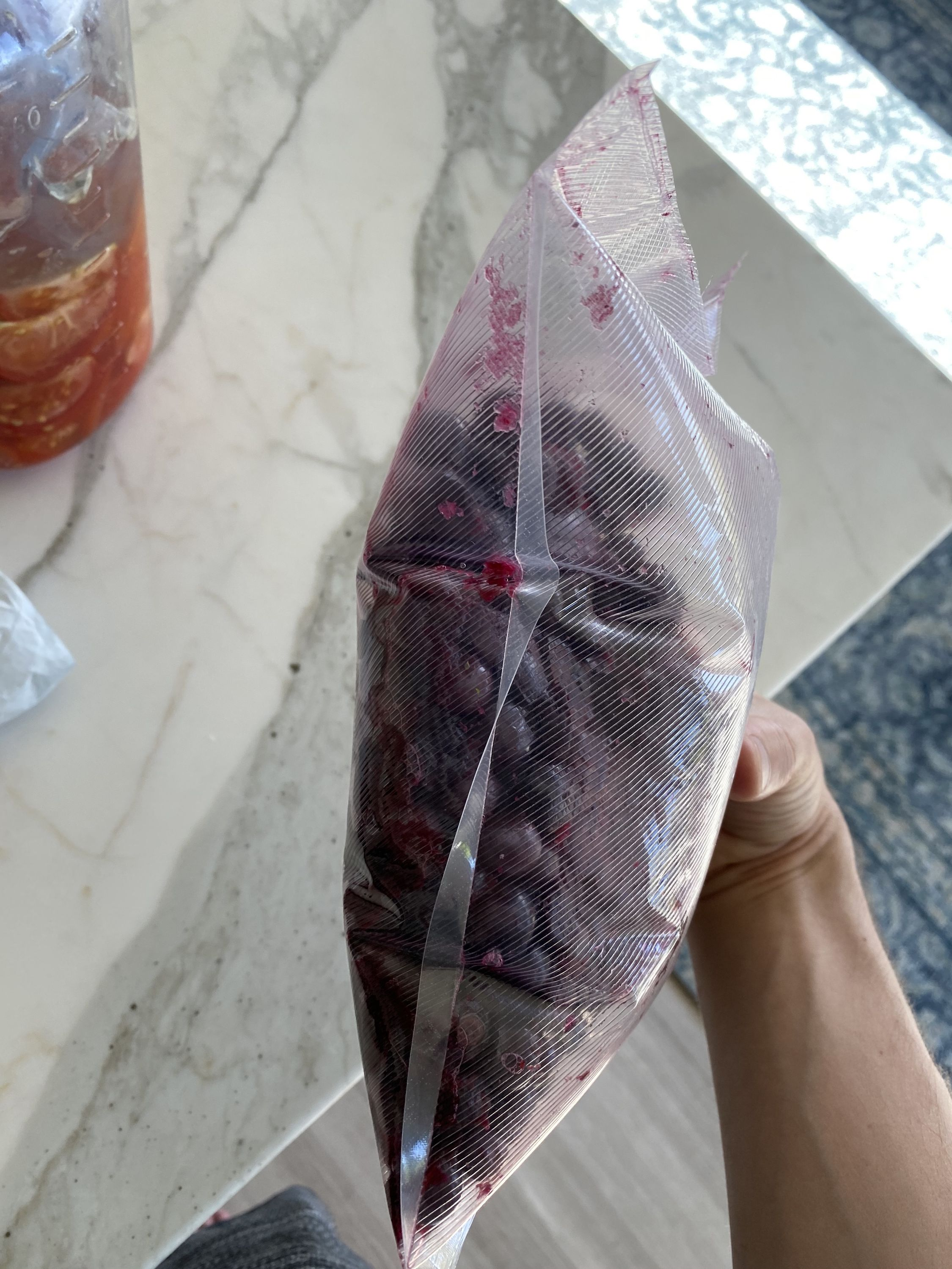 A vacuum-sealed bag of blueberries, puffy with gas