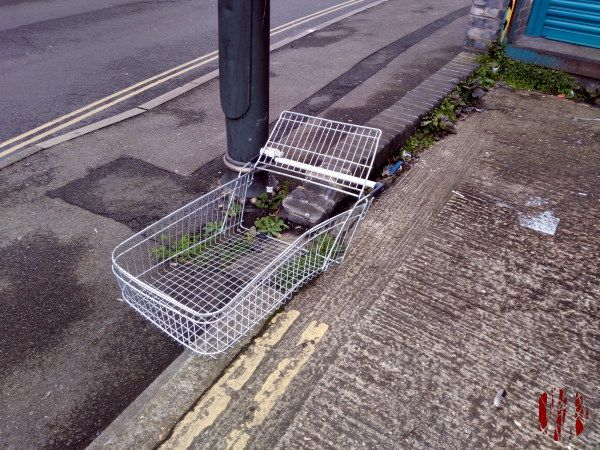 Photograph of supermarket trolley with it's lower chassis missing.