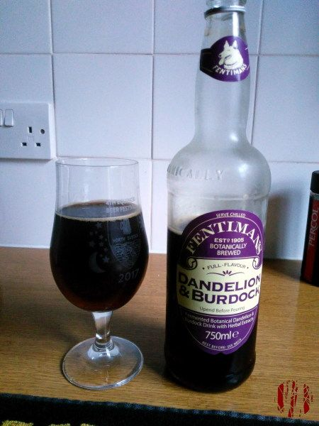 A glass of dandelion and burdock with the bottle it was poured from beside it on a kitchen counter top with power socket to the left.