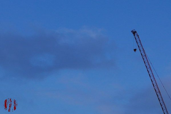 Just the top of a crane seen early morning against a blue sky with a thin cloud to the side.