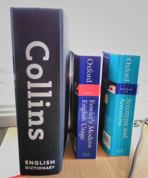 Photograph of a large Collins Dictionary, Fowler's Modern English Usage, and Oxford Guide To Synonyms And Antonyms