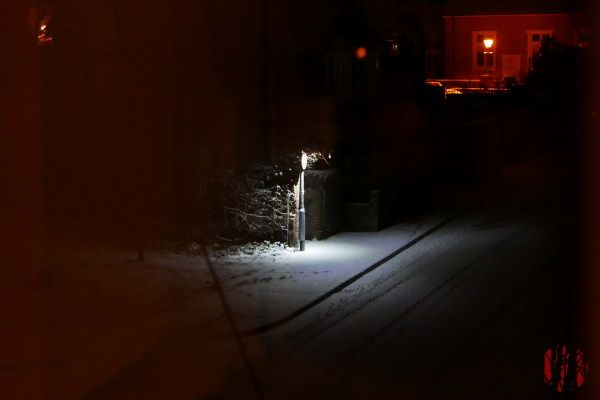 A no cycling sign sign lit by a light in an otherwise dark street at night showing the snow on the ground.
