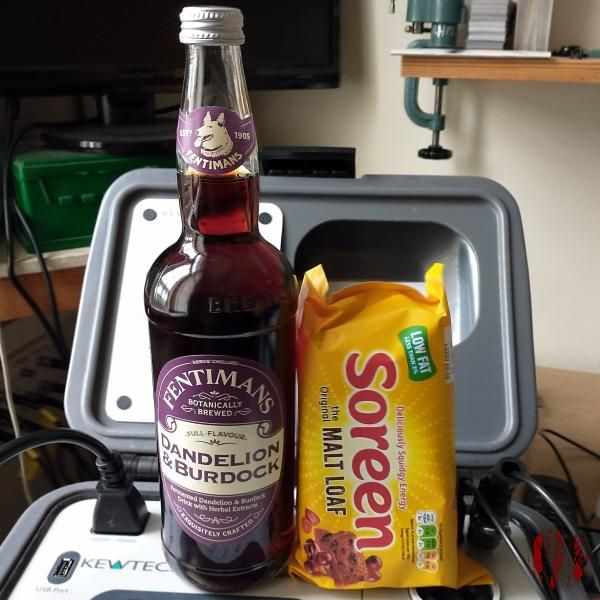A bottle of Dandelion & Burdock with a Malt Loaf propped up against it.