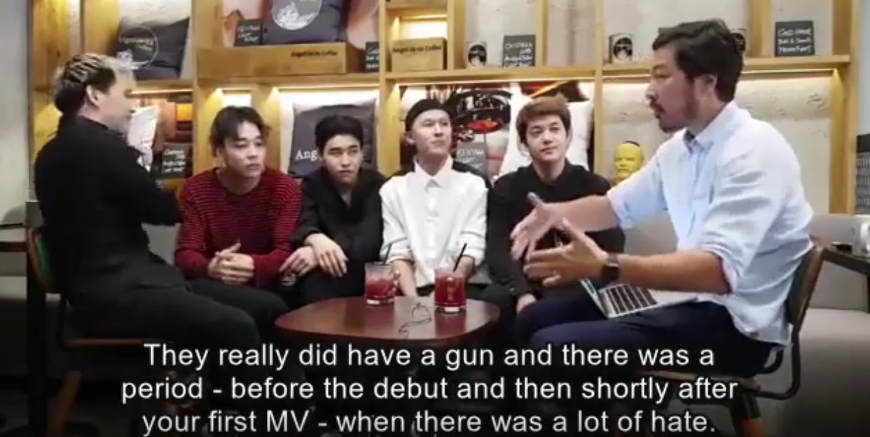 """Image of an interviewer saying to Ninety One, """"There really was a gun and there was a period, before the debut and then shortly after your first MV, where there was a lot of hate."""""""