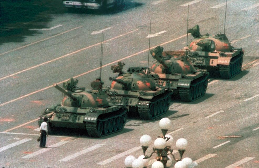 Man stands in front of column of tanks leaving Tiananmen Square