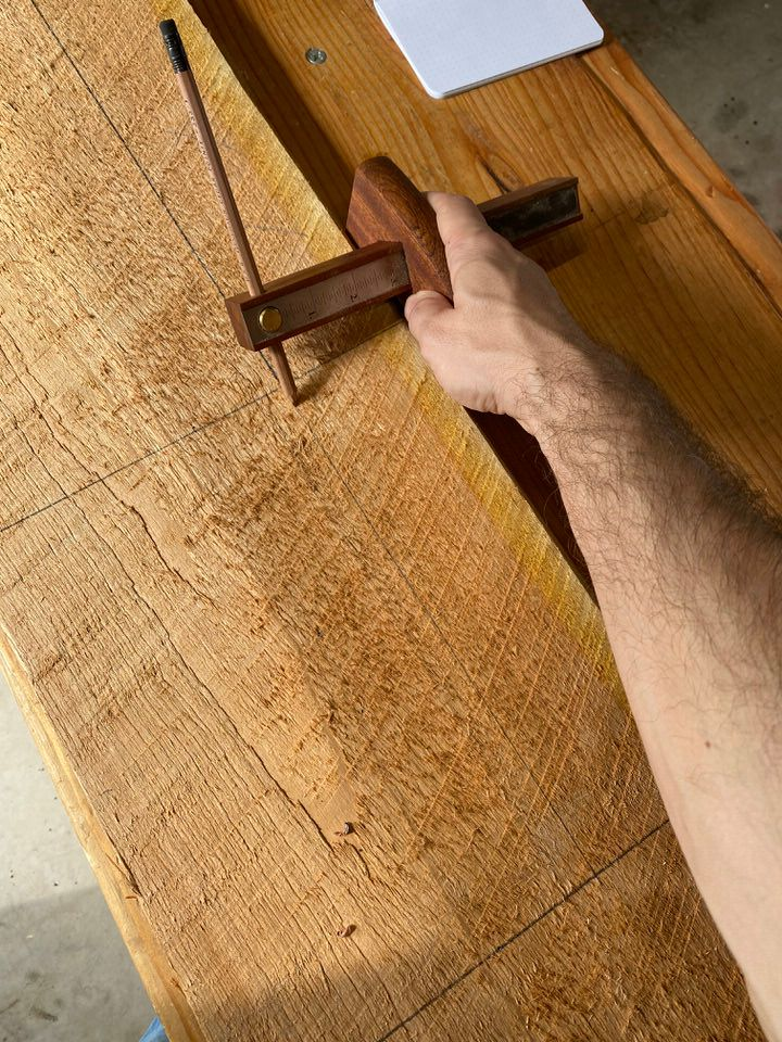 Marking gauge being used to mark out various parts of a project on a dimensioned cherry board.
